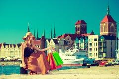 Modieuze vrouw die na het winkelen zitting met zakken rusten Stock Afbeeldingen