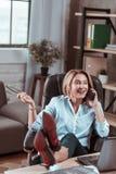 Modieuze vrouw die op de telefoon met vriend emotioneel voelen spreken stock foto