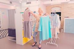 Modieuze vrouw die op middelbare leeftijd welke te kopen kleding beslissen stock foto