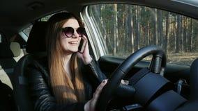 Modieuze vrouw die op mobiele telefoon spreken, die bij wiel van auto zitten stock footage