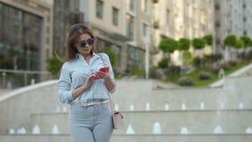 Modieuze vrouw die telefoon met behulp van bij fonteinachtergrond stock videobeelden