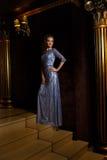 Modieuze vrouw die zich op gouden treden bevinden royalty-vrije stock foto
