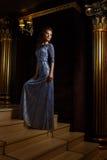 Modieuze vrouw die zich op gouden treden bevinden royalty-vrije stock afbeeldingen