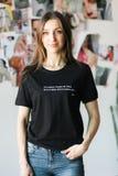 Modieuze vrouw in een zwarte t-shirt, die in een studio stellen stock foto
