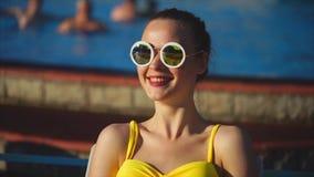 Modieuze vrouw in een zwempak en zonnebril glimlachen, die buiten in de zomer zitten stock videobeelden