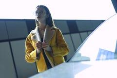 Modieuze vrouw in gele jasje en glazen Stellend op stadscentrum, door helder licht wordt aangestoken dat Womenswearmanier stock afbeelding