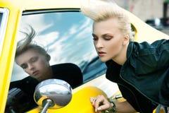 Modieuze vrouw met gele auto Royalty-vrije Stock Afbeeldingen