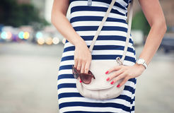 Modieuze vrouw met zak in haar handen en gestreepte kleding Stock Foto's