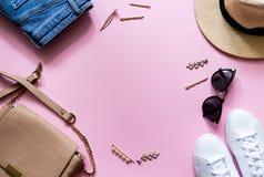 In modieuze vrouwelijke flatlay kleren Jeans, tennisschoenen, ronde zonnebril, gouden haarklem, zak en hoed Roze achtergrond royalty-vrije stock afbeelding