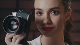 Modieuze vrouwenfotograaf die met retro fotocamera in camera in studio glimlachen stock videobeelden