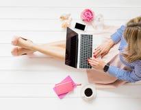 Modieuze vrouwenzitting op vloer en het gebruiken van laptop stock fotografie