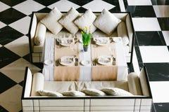 Modieuze witte eettafel en banken Minimalistisch binnenland in zwart-wit Zwart-wit concept Lege restaurantbovenkant Royalty-vrije Stock Foto's