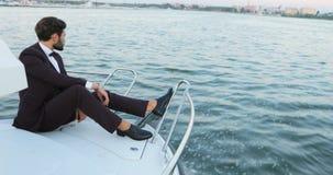 Modieuze zakenman op een jacht of boot tegen een overzees vervoer, zakenreis, technologie en van het mensenconcept Luxe stock video