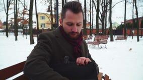 Modieuze zakenmanzitting op een bank in een de winterpark die een tablet met een aktentas trekken Knappe jonge mens die werken aa stock videobeelden