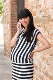 Modieuze zwangere vrouw op de telefoon Stock Foto