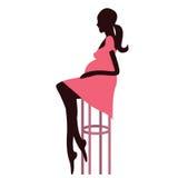 Modieuze zwangere vrouwenzitting op de barstoel Royalty-vrije Stock Foto's