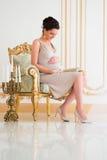 Modieuze zwangerschap Toekomstige moeder in een duur binnenland Stock Afbeelding