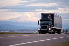 Modieuze zwarte moderne krachtige vrachtwagen met zwarte aanhangwagen toneelro Stock Fotografie