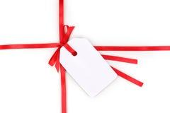 Modifica in bianco del regalo con l'arco sul nastro rosso del raso Fotografia Stock