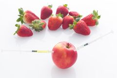 Modified food, fruits,apple and strawberries with punched needles and syringes / isolatet on a white background. Modified food, apple and strawberries with Royalty Free Stock Images