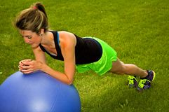 Modified Plank with an exercise ball. Young woman doing the plank with an exercise ball royalty free stock photography