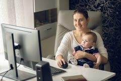 Modifiez la tonalité le dimage du jeune owman de sourire fonctionnant à la maison le bureau et tenant son fils de bébé photographie stock