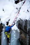 Modig isklättrare som klättrar en med is vattenfall i italienska fjällängar Royaltyfri Fotografi