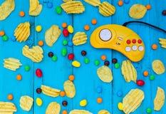 Modig kontrollant, chiper och godis på en blå träbakgrund Arkivfoto