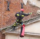 Modiga brandmän som klättrar med rep och klättrar på utrustning Royaltyfri Fotografi