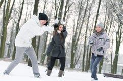 modigt leka kastar snöboll vinterungdommen Arkivfoto