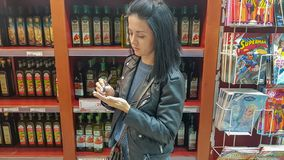 Modiin / Israel - December 30 2018: Young attractive brunette woman shopping in supermarket, choosing olive oil, using notebook w. Young attractive brunette royalty free stock photos