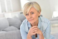 Modische blonde ältere Frau zu Hause Lizenzfreies Stockfoto