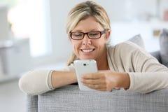 Modische blonde Frau, die Smartphone verwendet Lizenzfreie Stockfotos