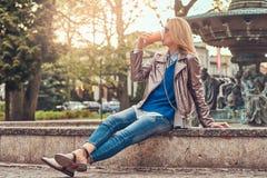 Modische blonde Frau entspannt sich, trinkenden Mitnehmerkaffee im Freien beim Sitzen auf der Bank im Stadtpark Lizenzfreie Stockfotografie