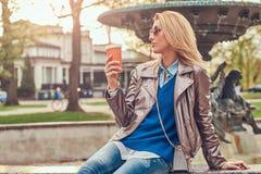 Modische blonde Frau entspannt sich, trinkenden Mitnehmerkaffee im Freien beim Sitzen auf der Bank im Stadtpark Lizenzfreie Stockfotos