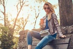 Modische blonde Frau entspannt sich, trinkenden Mitnehmerkaffee im Freien beim Sitzen auf der Bank im Stadtpark Stockfotografie