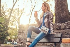 Modische blonde Frau entspannt sich, trinkenden Mitnehmerkaffee im Freien beim Sitzen auf der Bank im Stadtpark Lizenzfreies Stockfoto