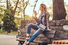 Modische blonde Frau entspannt sich, trinkenden Mitnehmerkaffee im Freien beim Sitzen auf der Bank im Stadtpark Lizenzfreies Stockbild