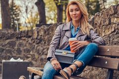 Modische blonde Frau entspannt sich, trinkenden Mitnehmerkaffee im Freien beim Sitzen auf der Bank im Stadtpark Stockfotos