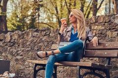 Modische blonde Frau entspannt sich, trinkenden Mitnehmerkaffee im Freien beim Sitzen auf der Bank im Stadtpark Stockbild