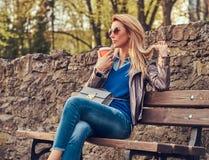 Modische blonde Frau entspannt sich, trinkenden Mitnehmerkaffee im Freien beim Sitzen auf der Bank im Stadtpark Lizenzfreie Stockbilder