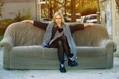 Modische Frau, die auf alter Couch in der Straße sitzt Stockfotografie