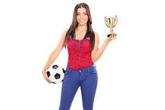 Modische Frau, die einen Fußball und eine Trophäe hält Stockfotografie