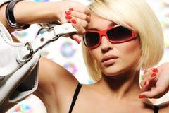 Modische Frau mit dem roten Sonnenbrilleanhalten Stockfotografie