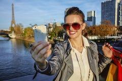 Modische Frau mit der Einkaufstasche, die selfie mit Telefon in Paris nimmt Stockbilder