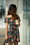 Modische Frau mit heißer Getränkstellung nahe Geschäft lizenzfreie stockbilder