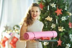 Modische Hausfrau mit Eignungsgang nahe Weihnachtsbaum stockfoto