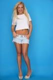 Modische junge blonde Frau in den Denimkurzen hosen Stockfoto