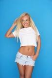Modische junge blonde Frau in den Denimkurzen hosen Lizenzfreie Stockfotos
