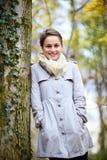 Modische junge Frau, die neben einem Baum steht Lizenzfreies Stockbild